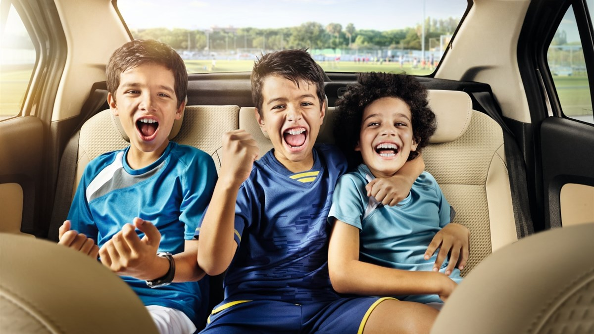 Happy kids sitting on the back seat of Renault SYMBOL