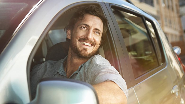Renault Confidence - A man with a beard smiling, leaning on his car door